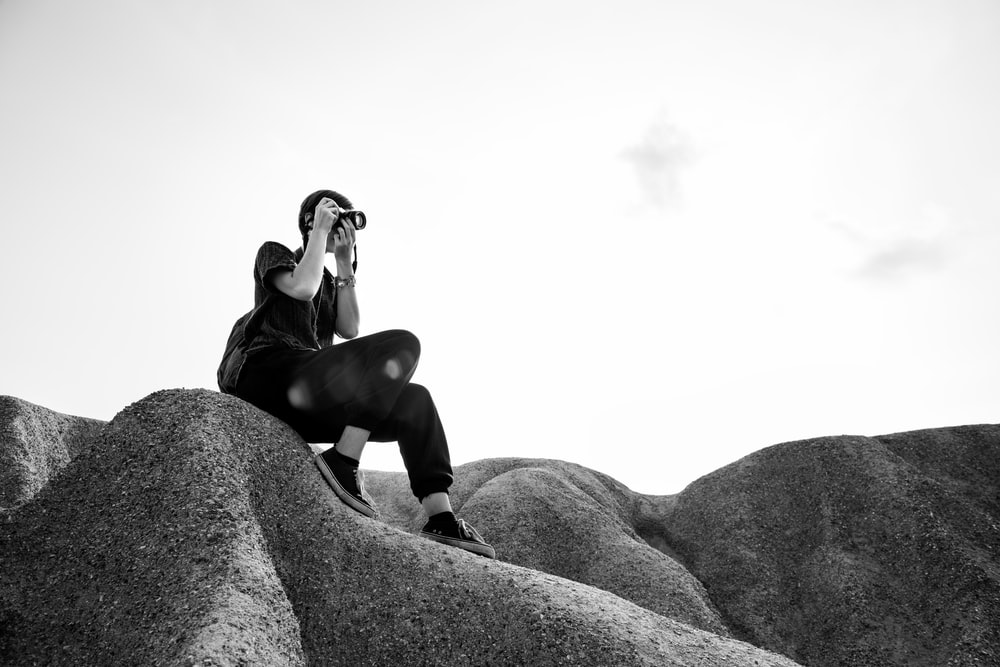 grayscale photography of sitting woman taking photo