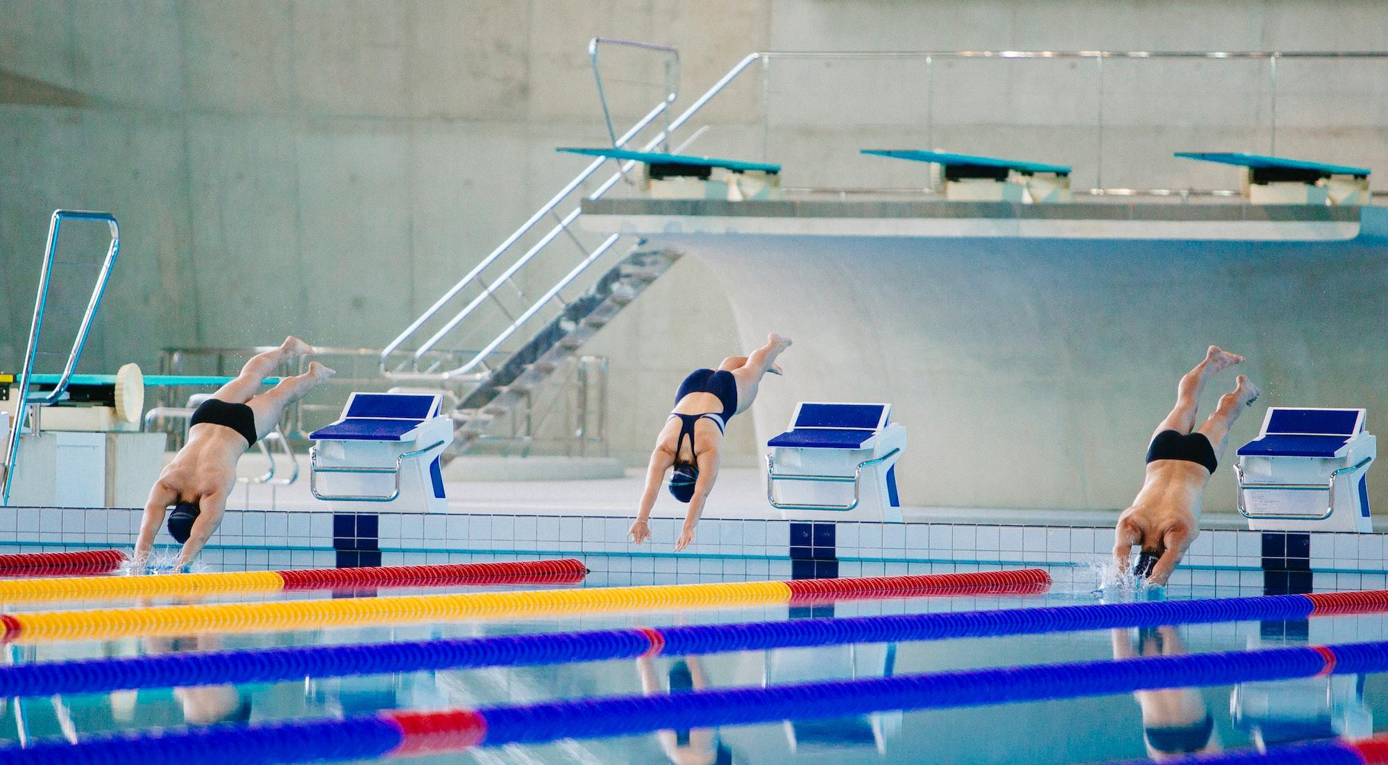 Três atletas de natação mergulhando numa piscina olímpica.
