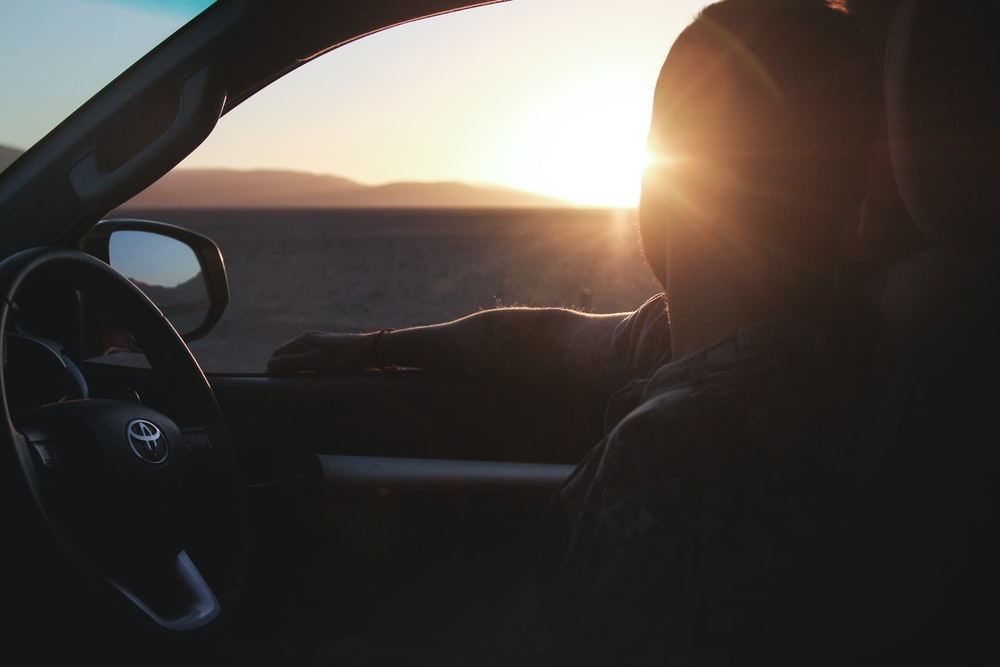 silhouette of man riding in Toyota car looking at sunset