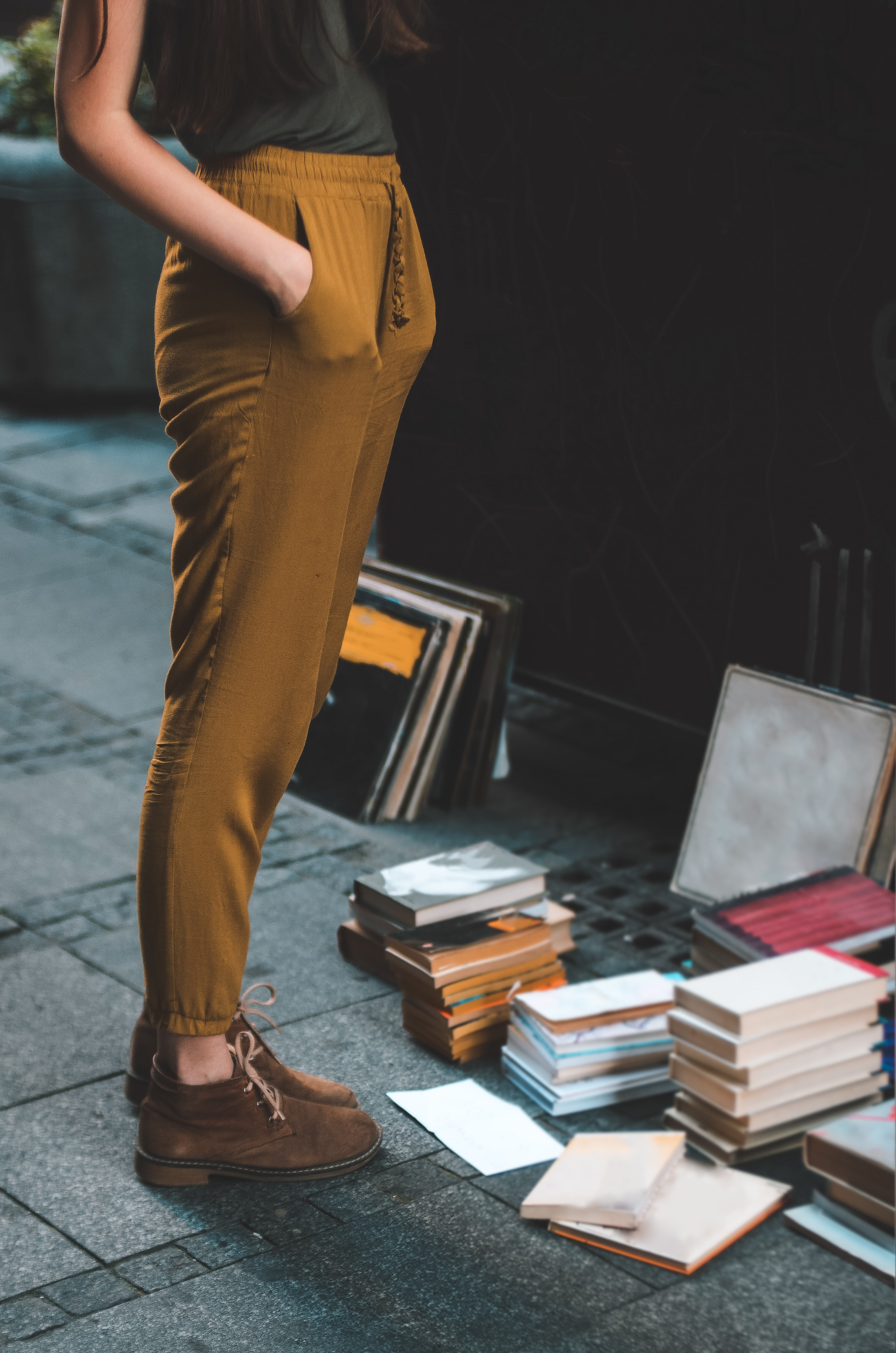 person wearing brown pants beside assorted book lot