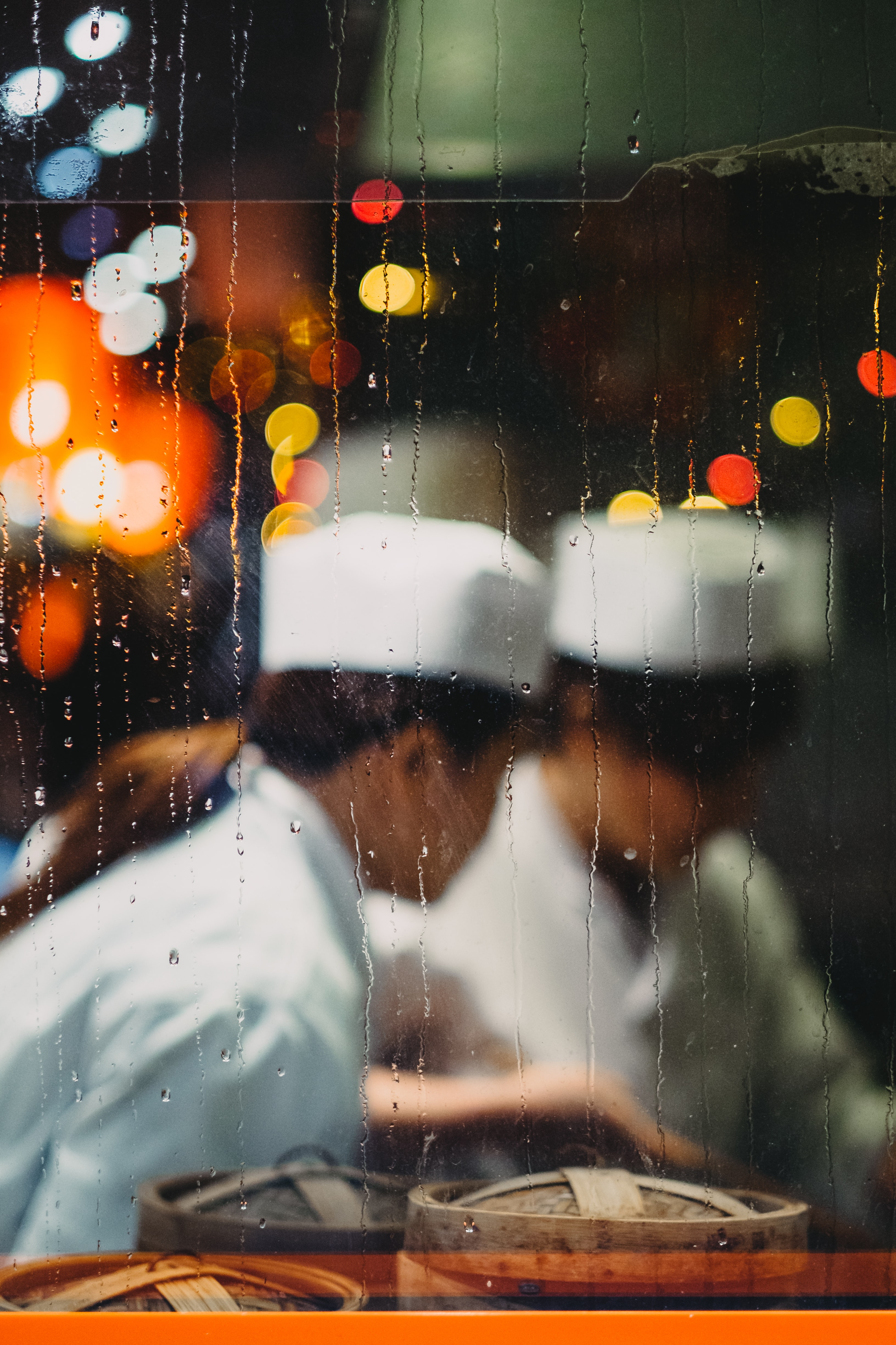two persons in white hats taken from glass frame with waterdrops