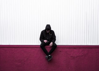 man sitting on purple wall
