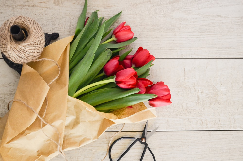 red tulip flowers bouquet on brown wooden pallet