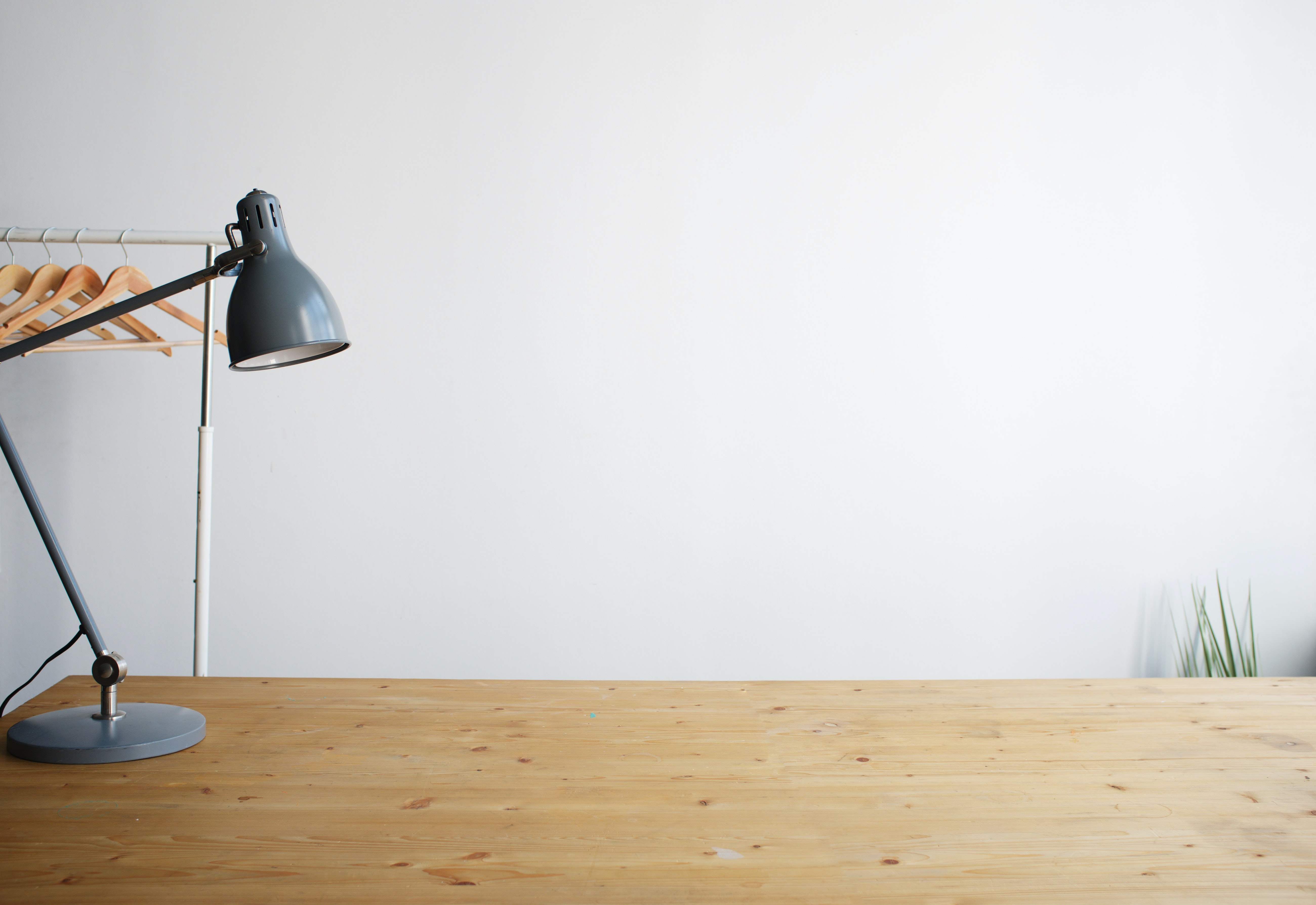 gray balanced-arm lamp on brown wooden table