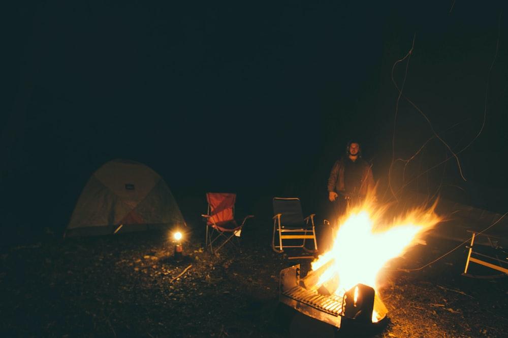 man near bonfire during nighttime