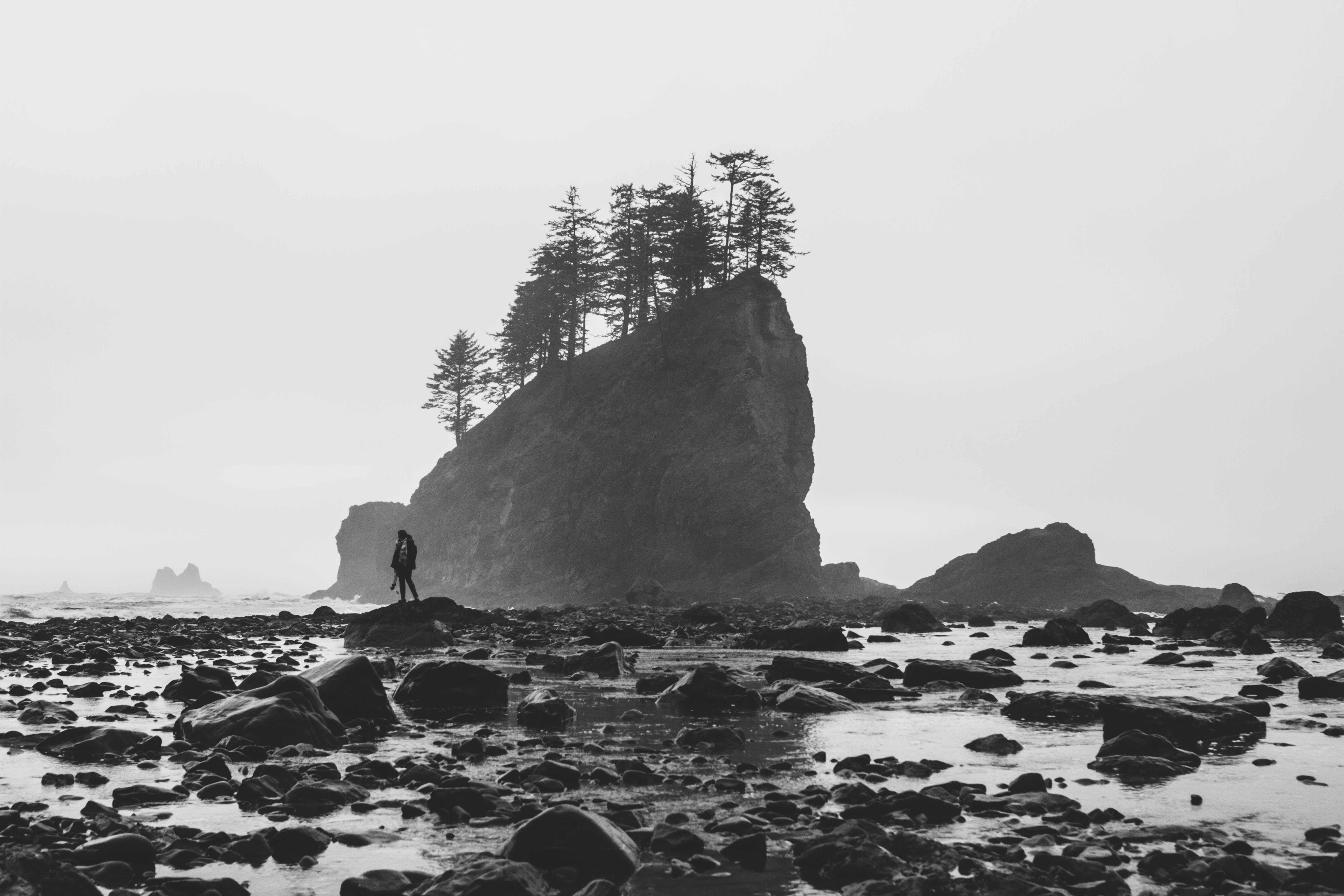 grayscale photography of person on rock formation