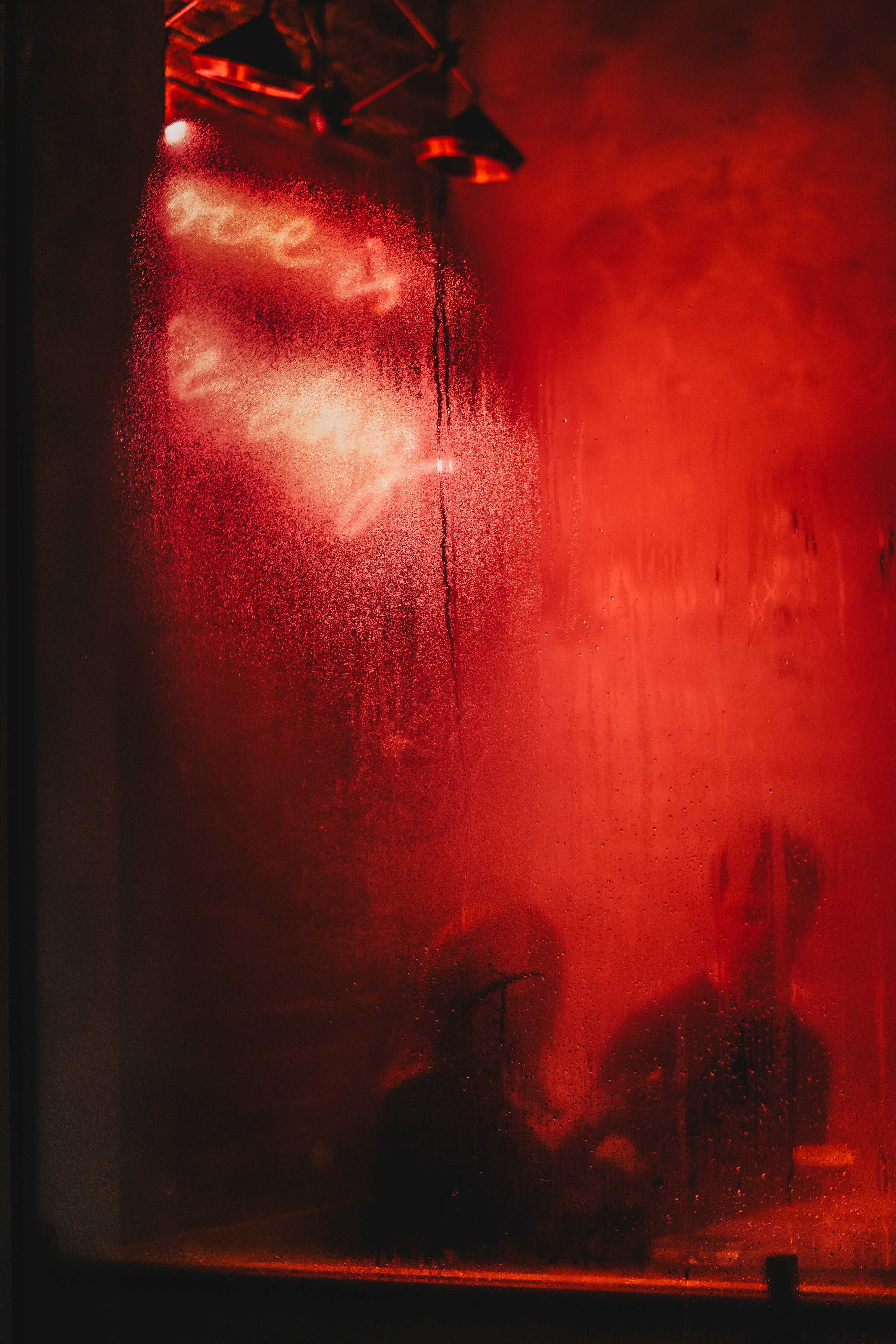 man and woman sitting at a table behind red glass window