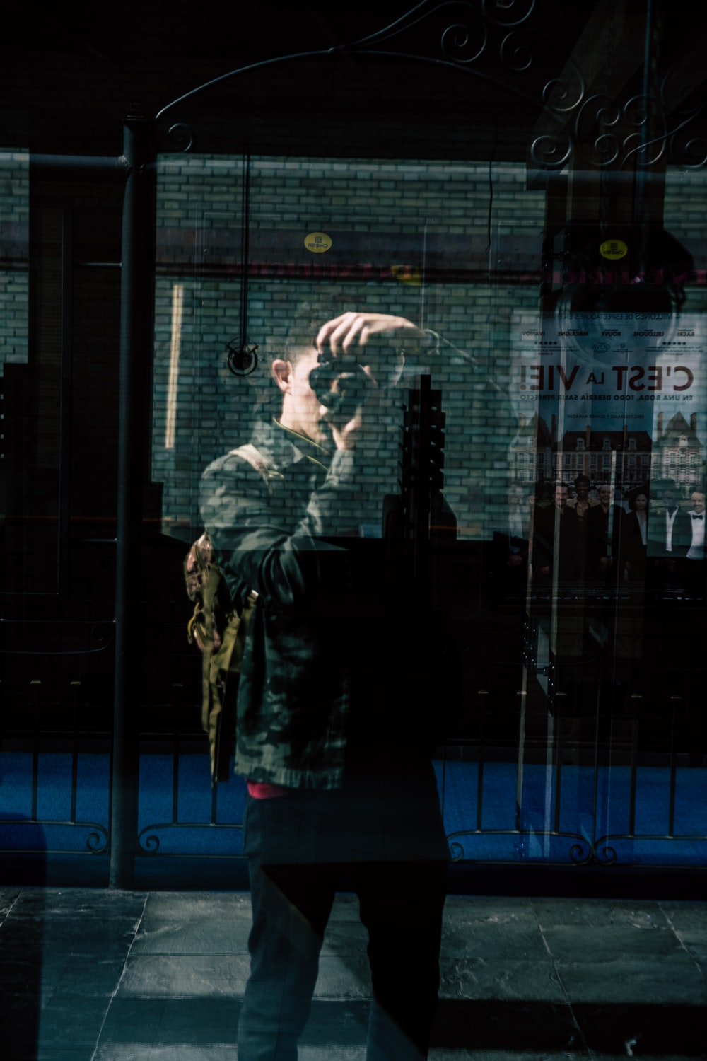 man taking photo himself by reflecting on glass wall