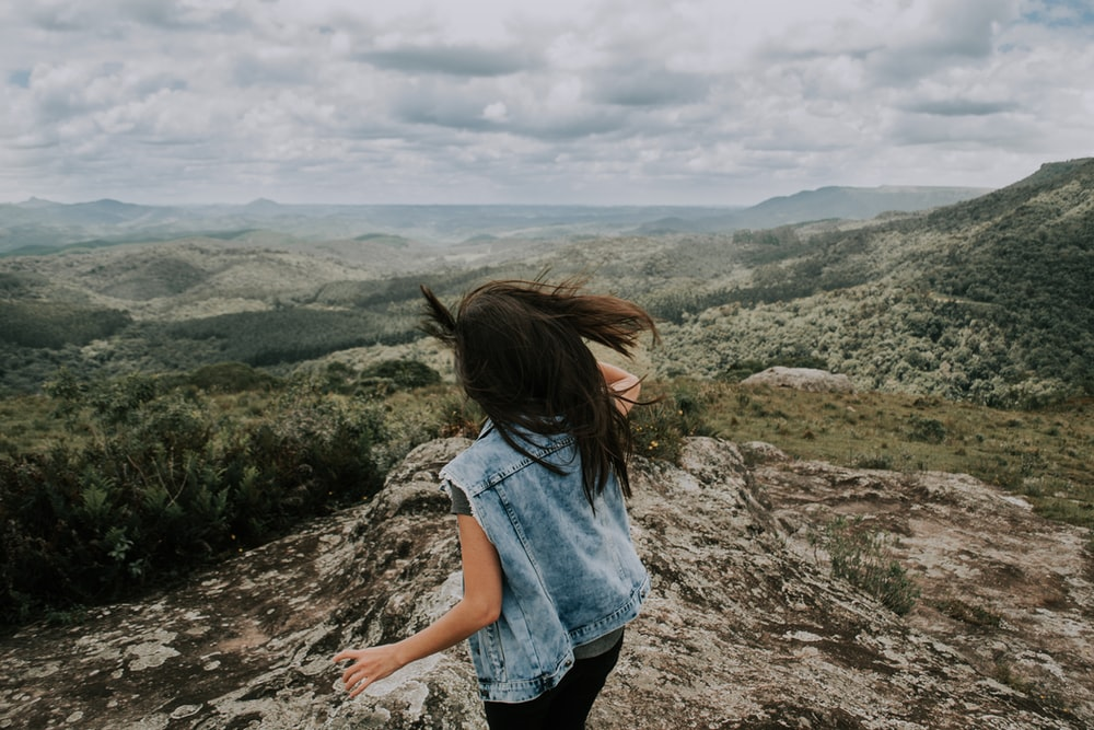 woman wearing blue denim jacket standing on the cliff