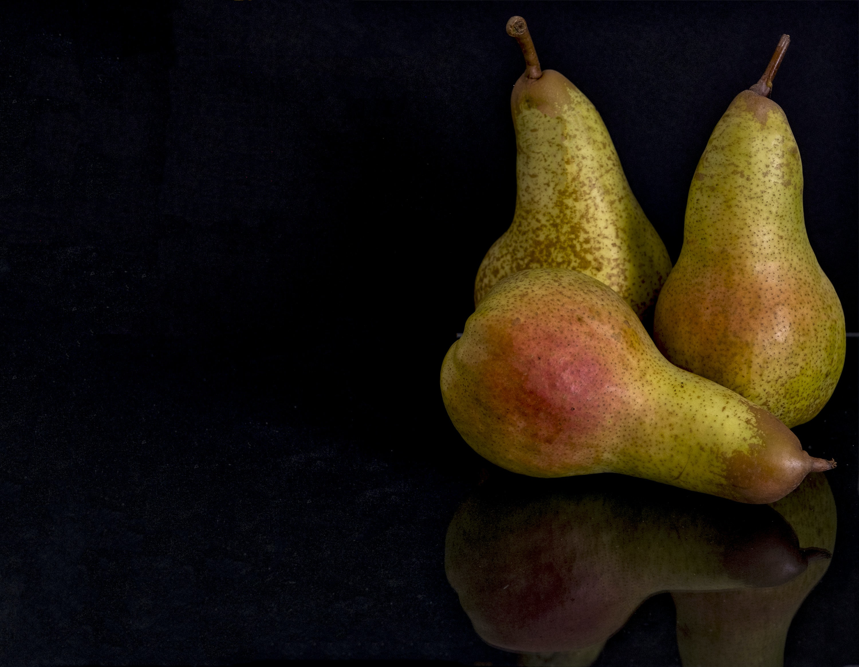 selective focus photography of three pears