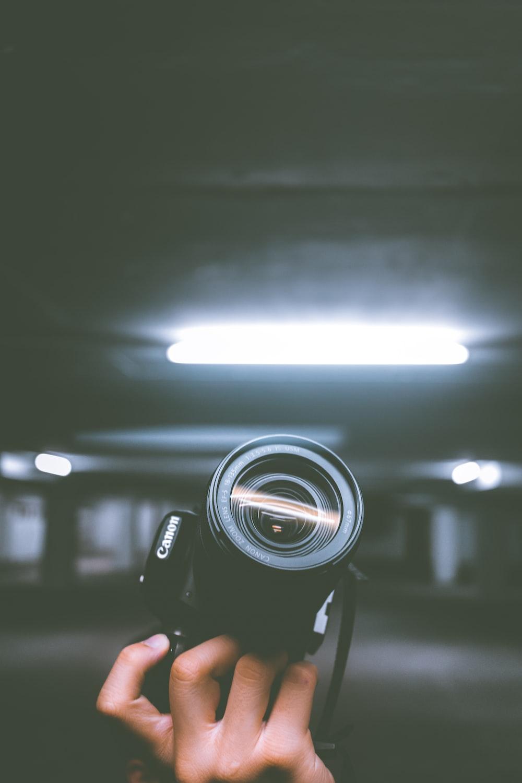 person holding black Canon DSLR camera inside indoor vehicle garage