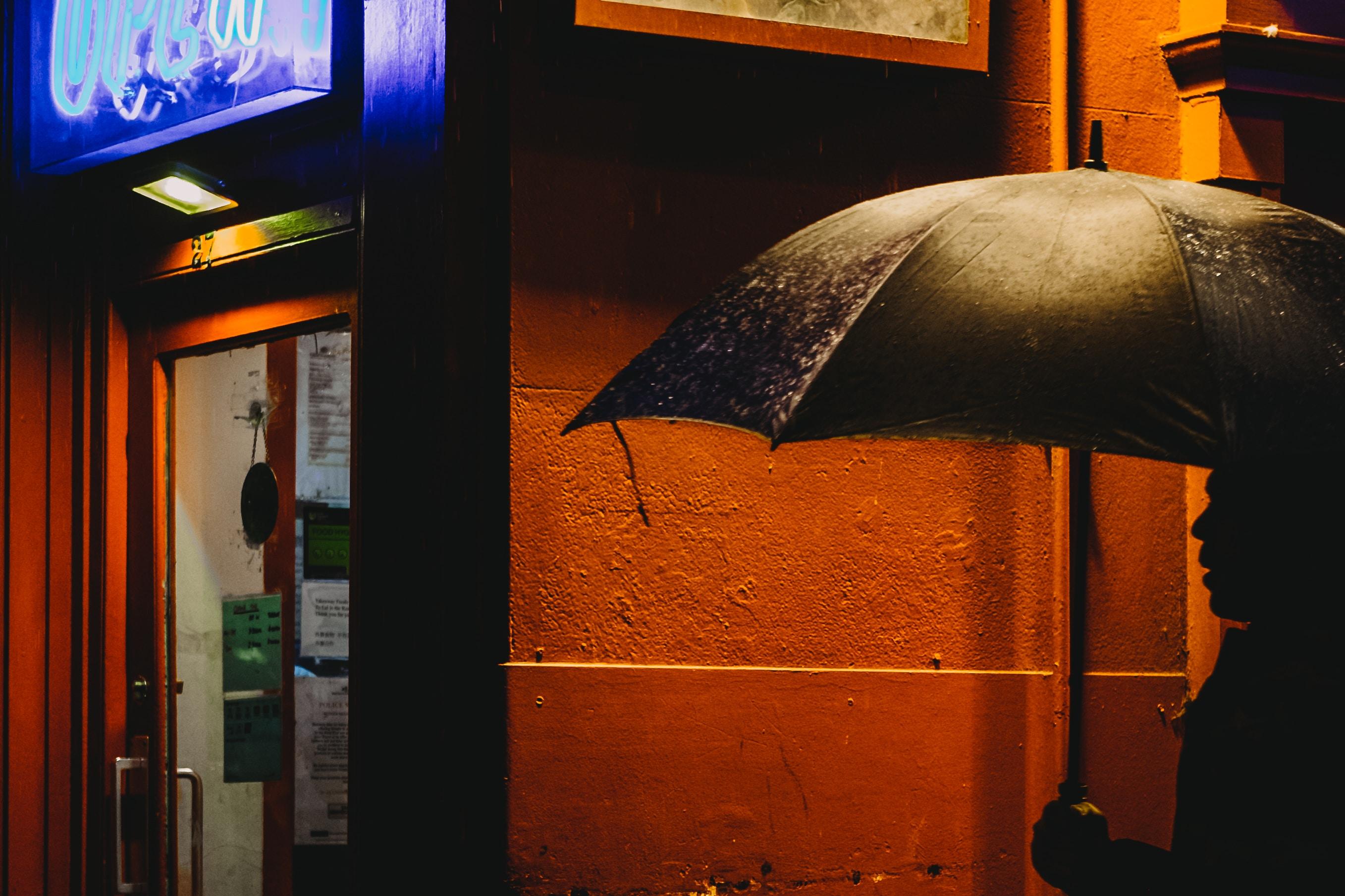 silhouette of person holding umbrella