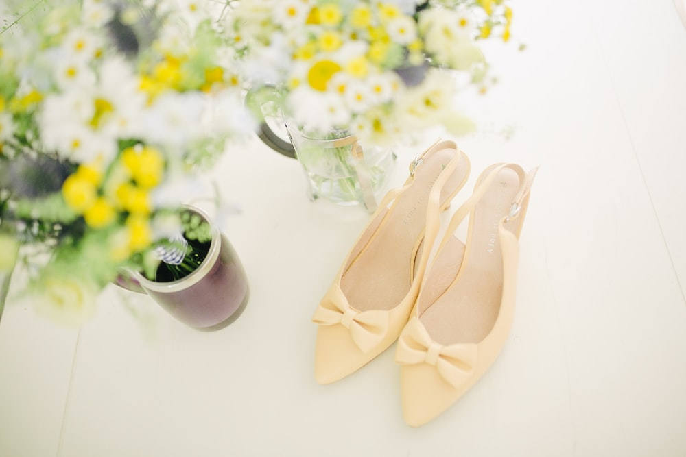 pair of women's beige pointed-toe slingback pumps with ribbons near flower vase