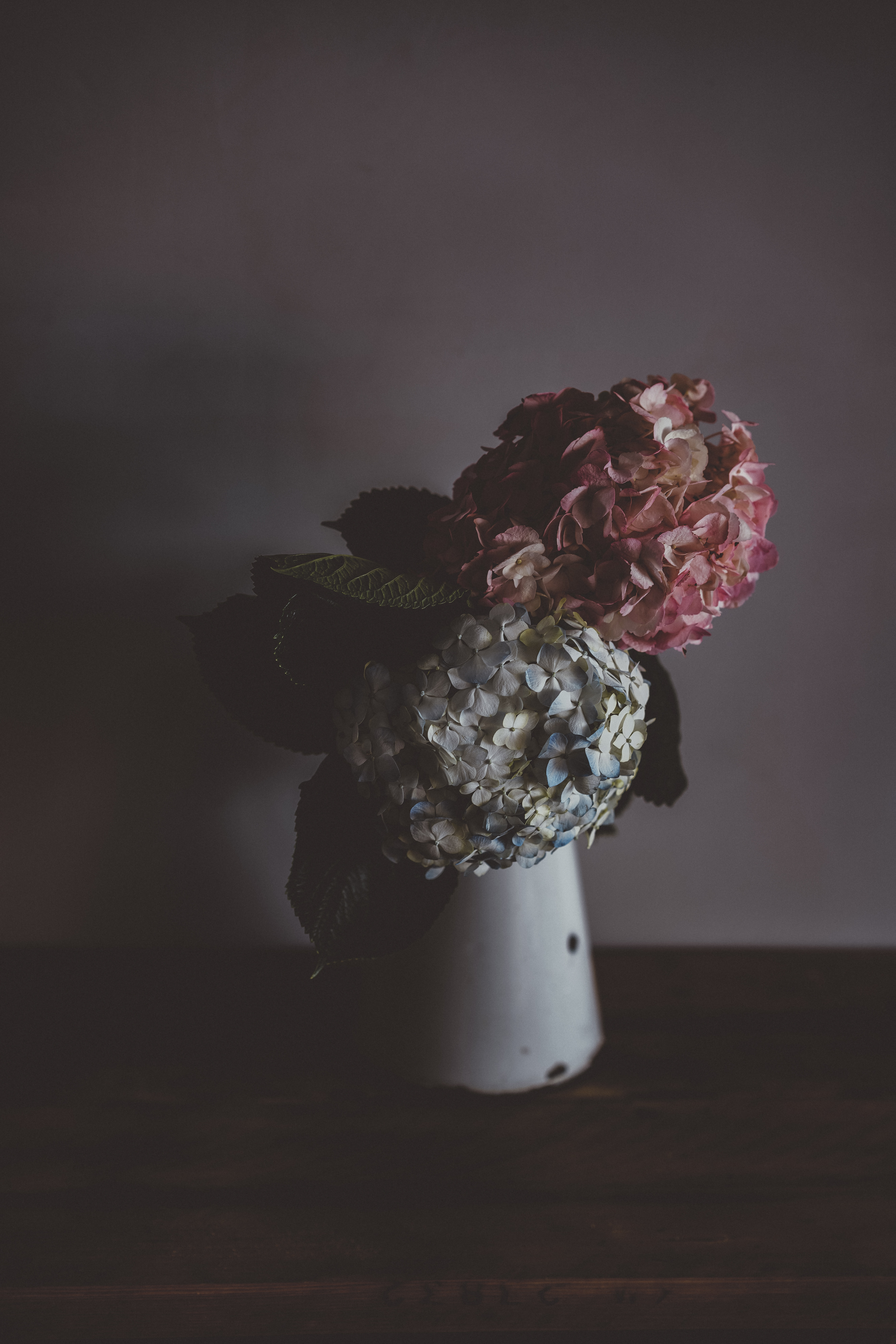 gray and pink flowers on white vase