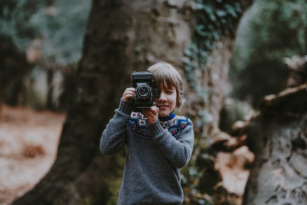 boy holding camera near brown tree during daytime