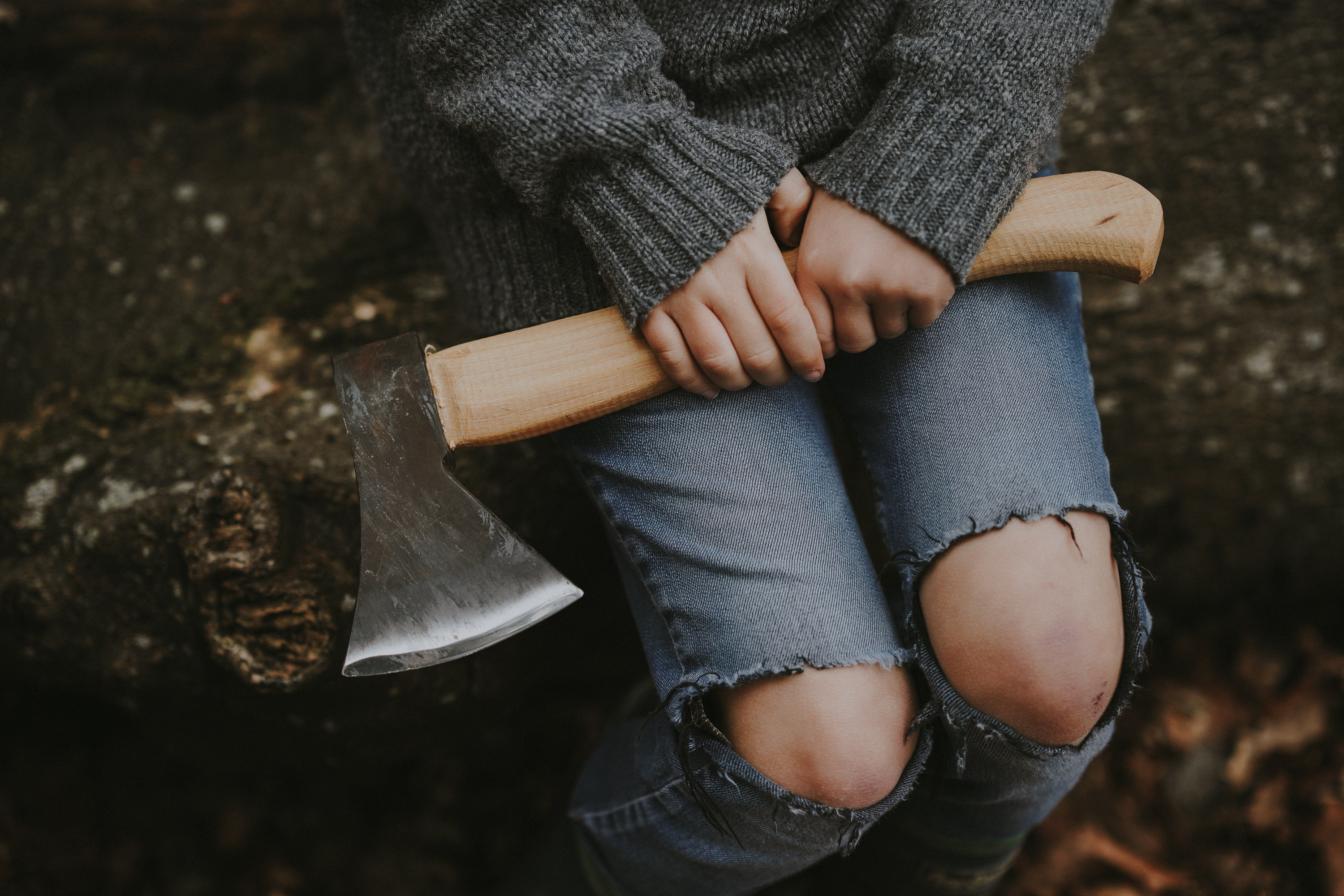 person wears grey knit sweatshirt sitting down while holding brown axe