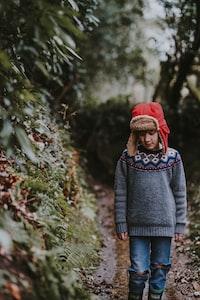 boy standing beside plants
