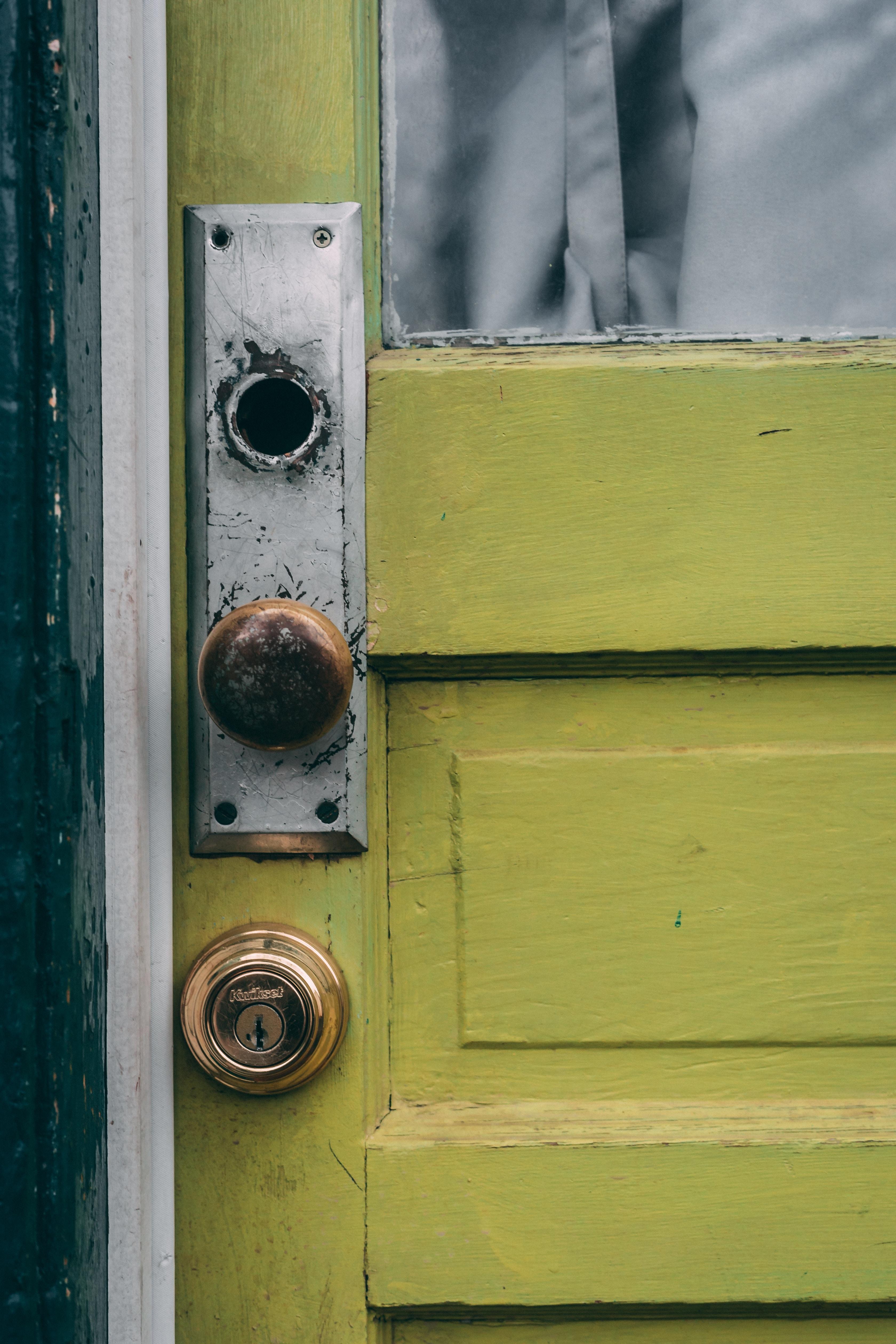 brown door knob in green wooden door