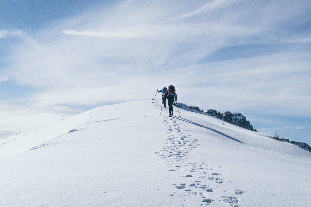 two person climbing on mountain covered snow