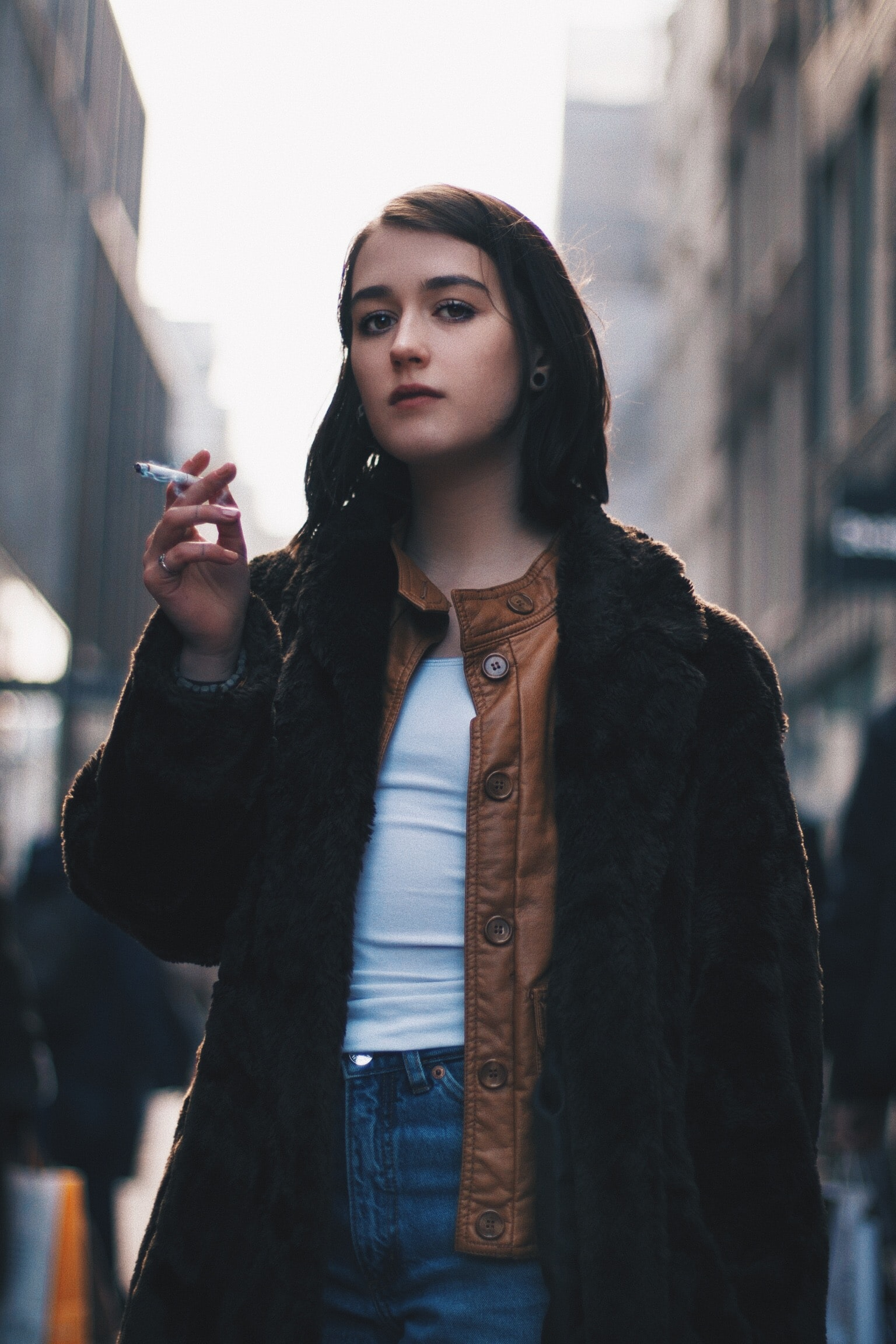 woman wearing black coat and holding cigarette stick during daytime