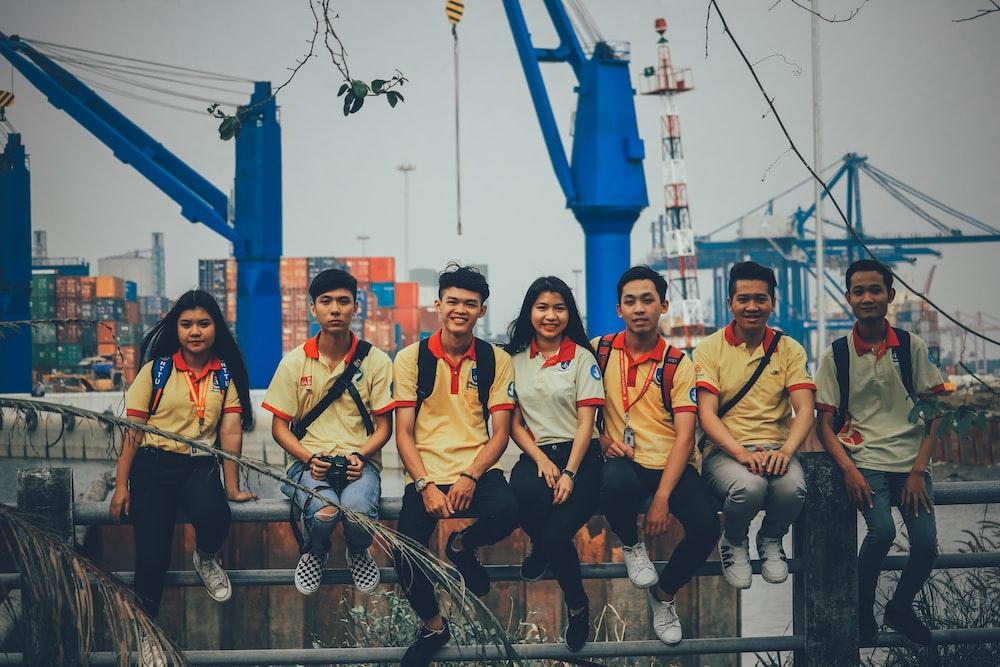 group of people sitting on metal railings