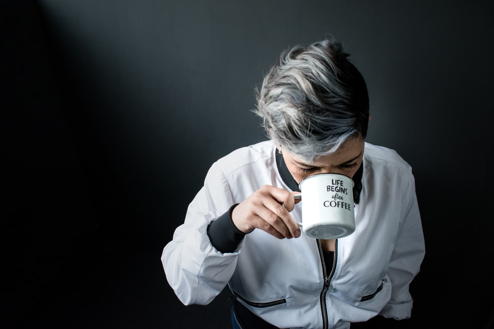 woman holding mug in drinking gesture