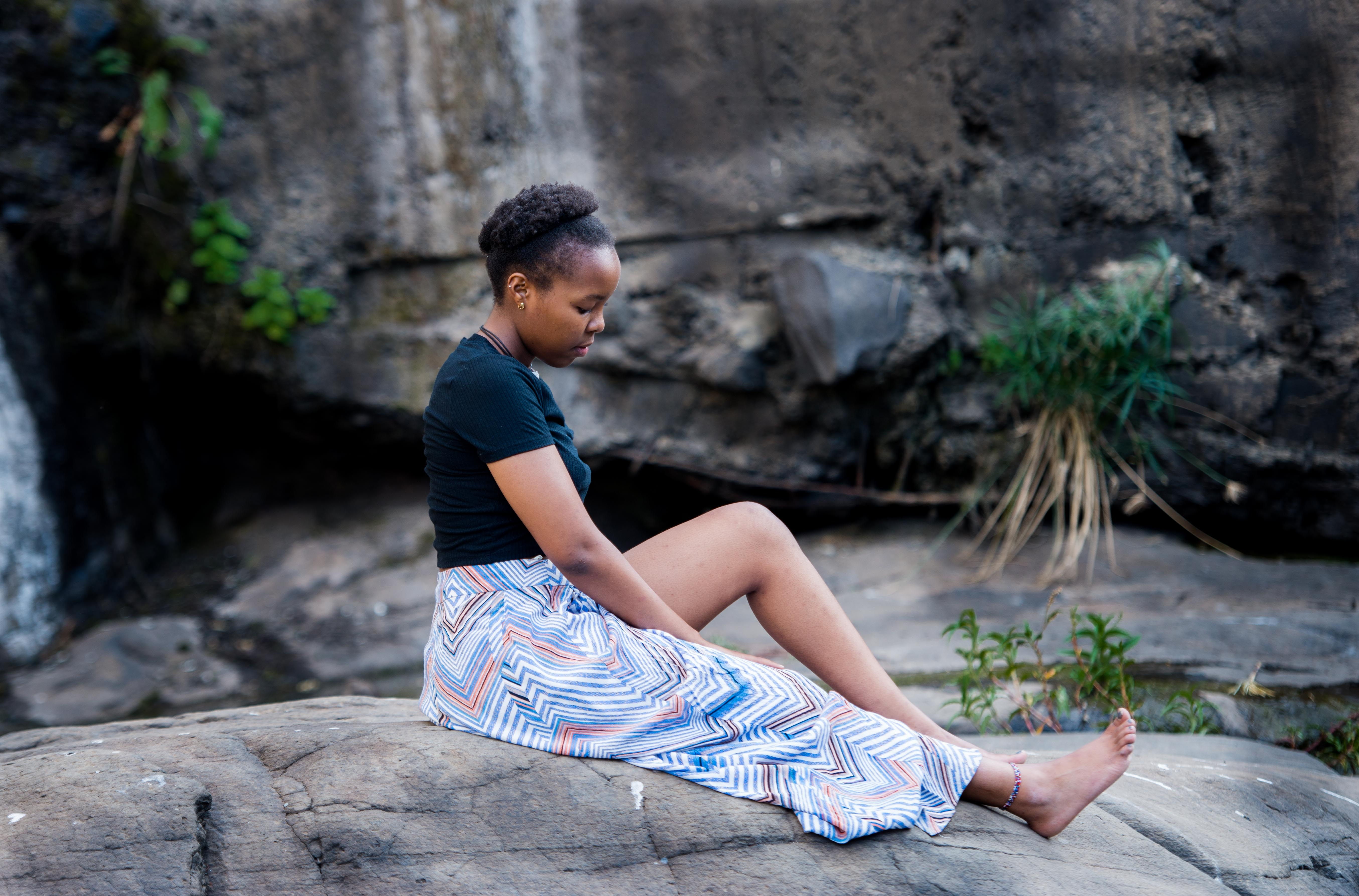 woman sitting on rock near cliff during daytime
