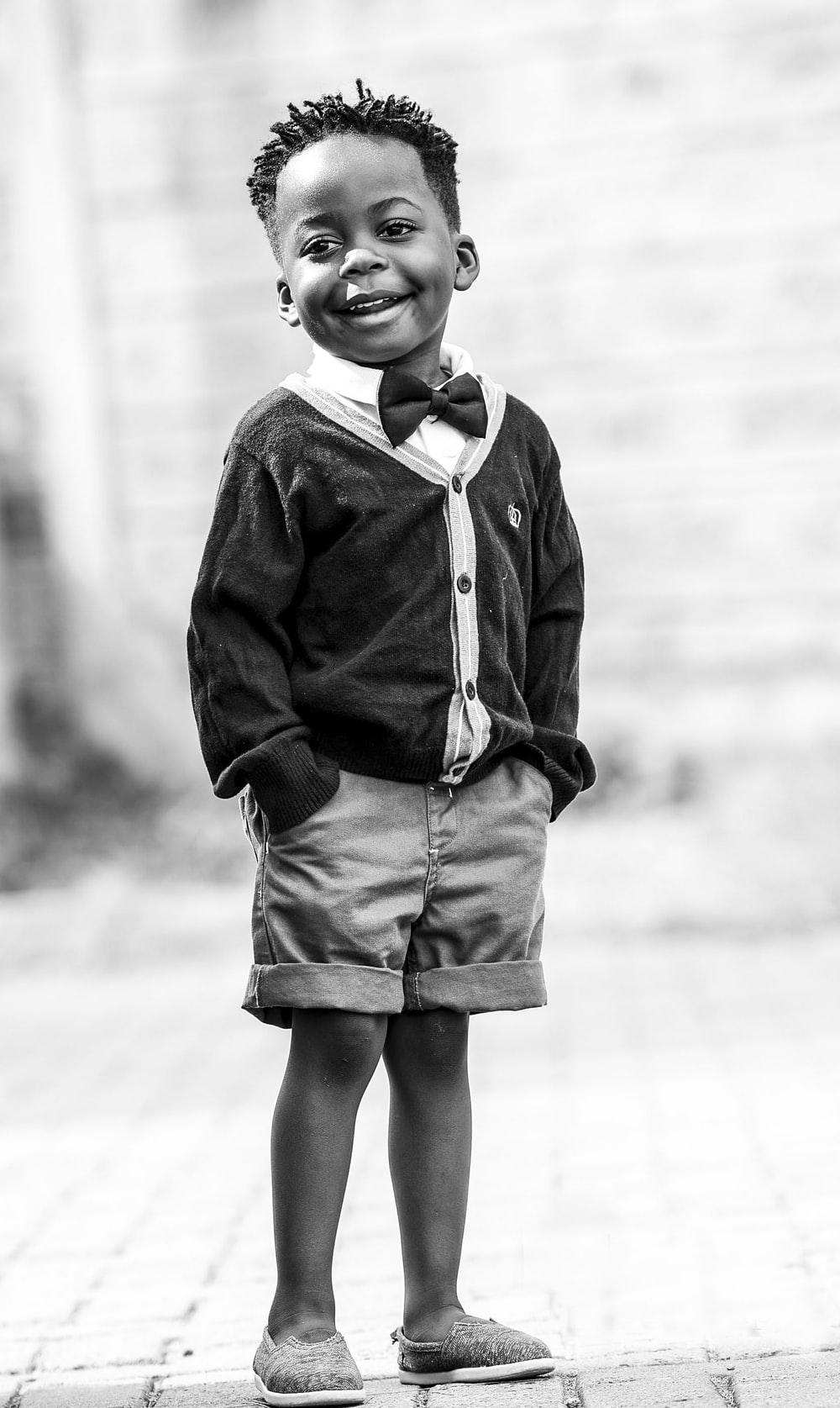 grayscale photo of boy in black button-up cardigan and shorts
