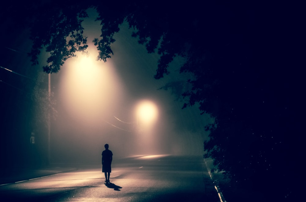 silhouette of person standing on concrete road with streetlights turned on during nighttime