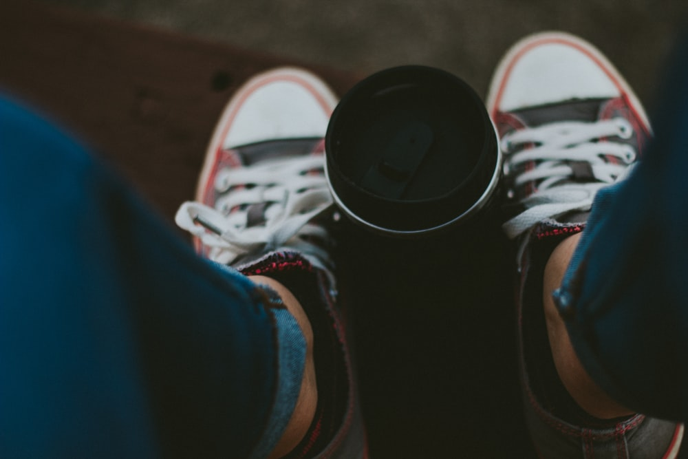 selective focus photography of person's sneakers beside tumbler
