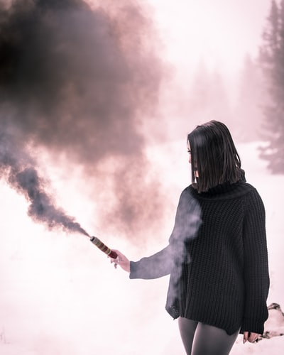 woman in black knit long-sleeved shirt using black stick with smoke