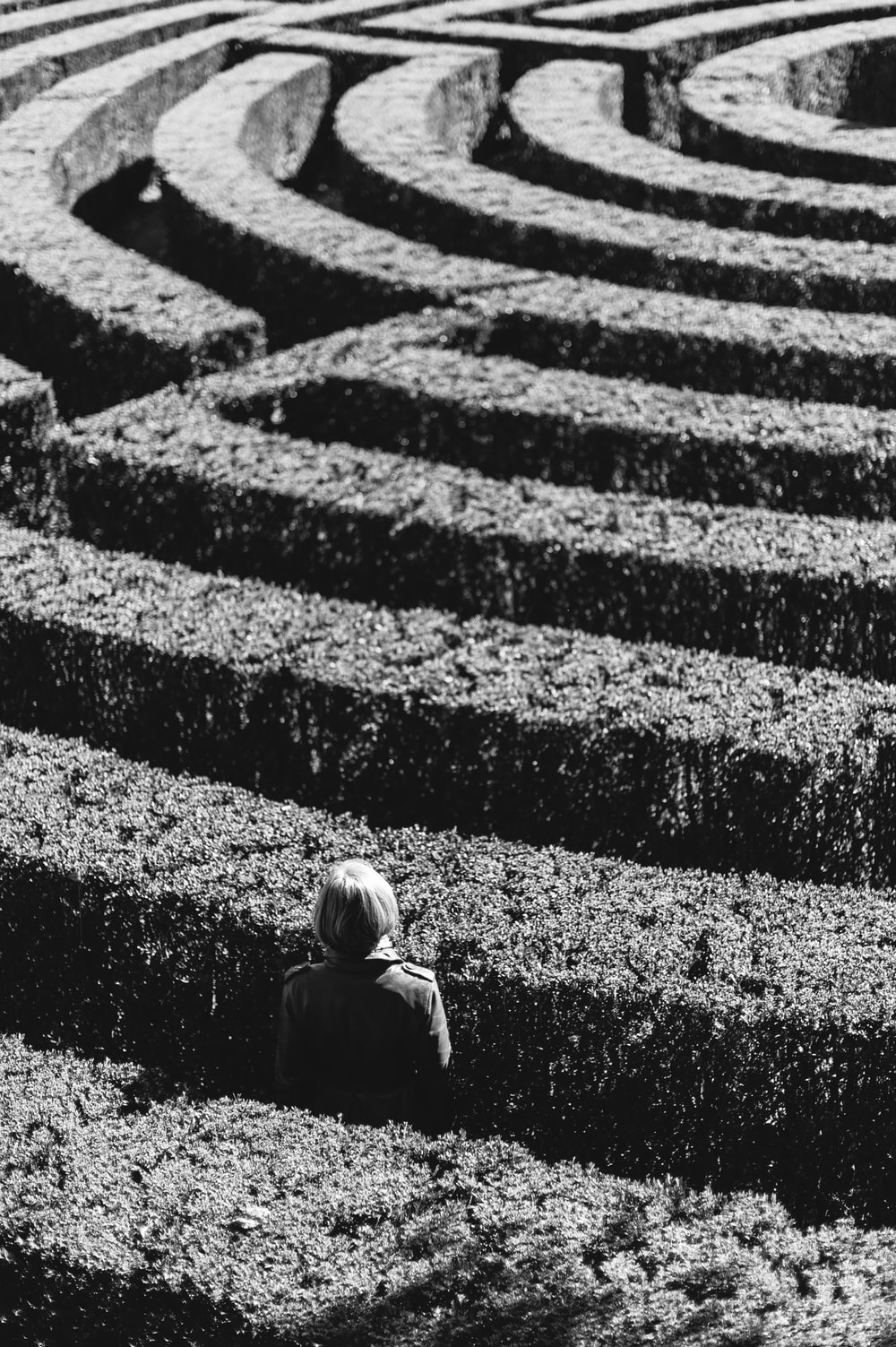 grayscale photo of person inside the plant formation