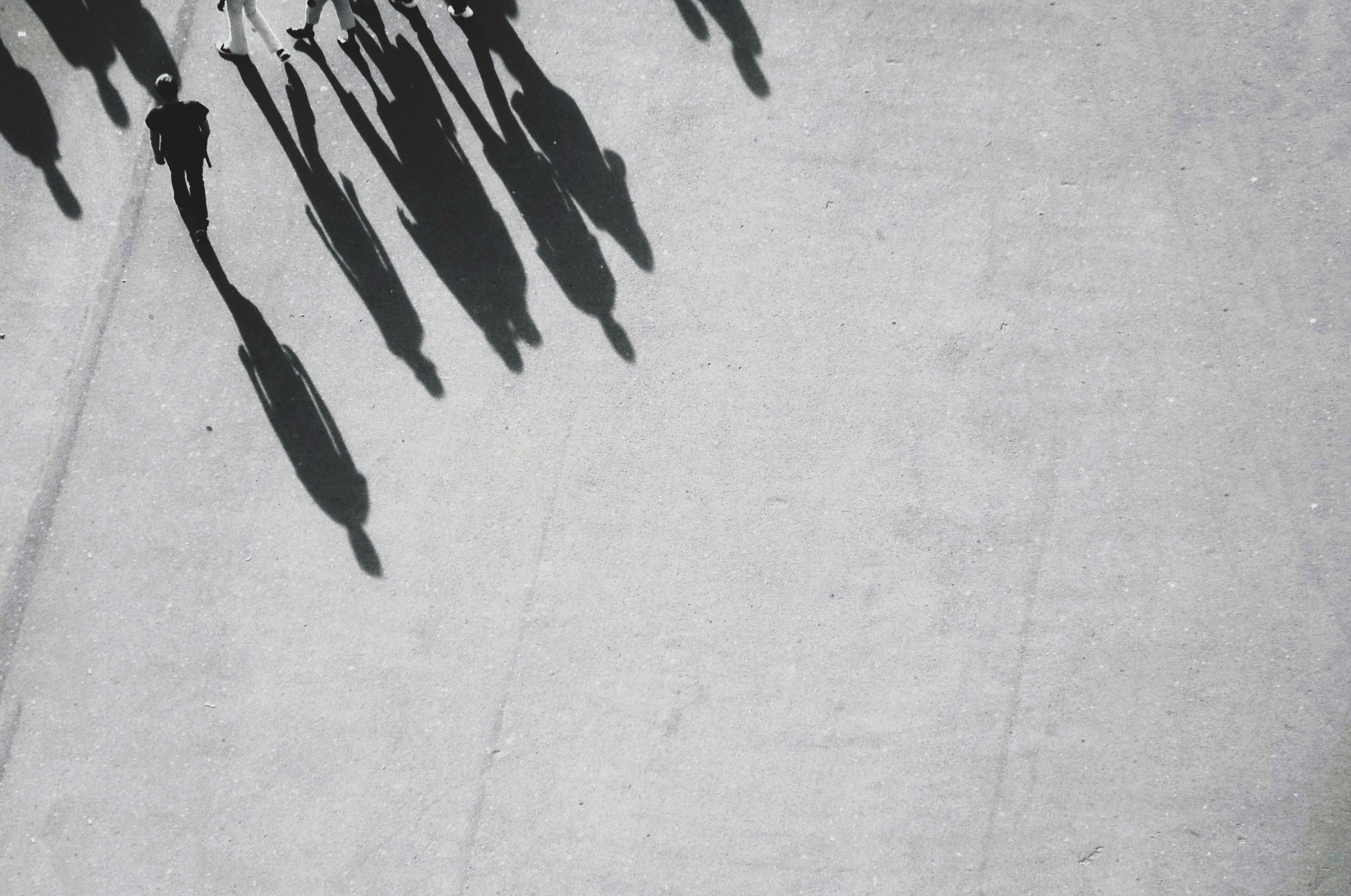 grayscale photography of shadow of people walking