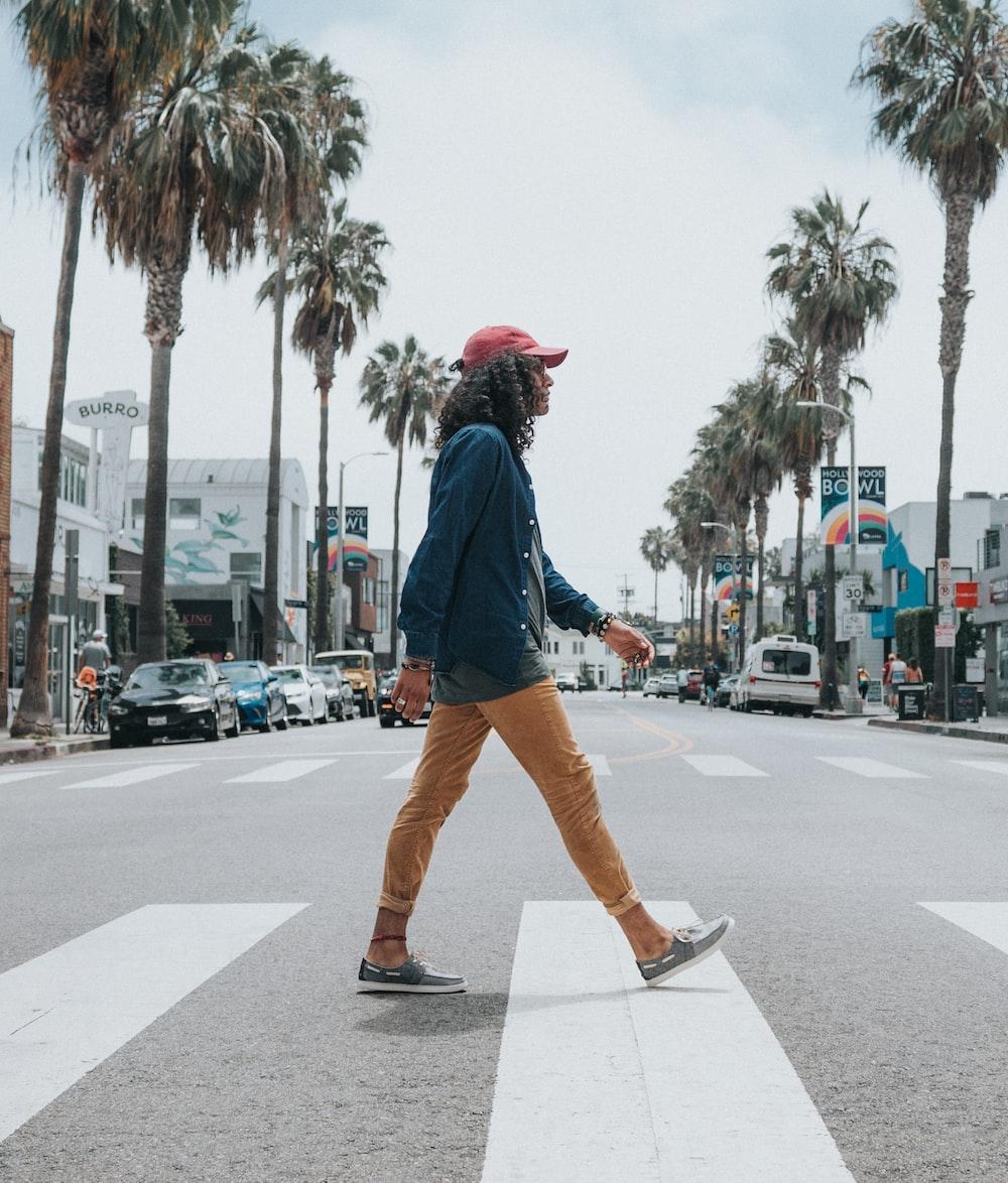 man wearing red cap crossing street
