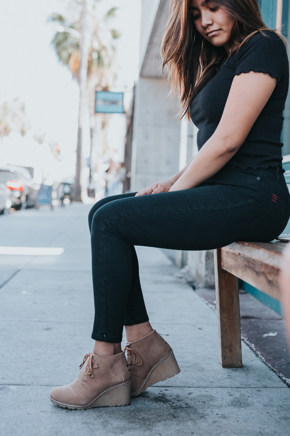 woman in black t-shirt and black pants sitting on brown wooden bench during daytime