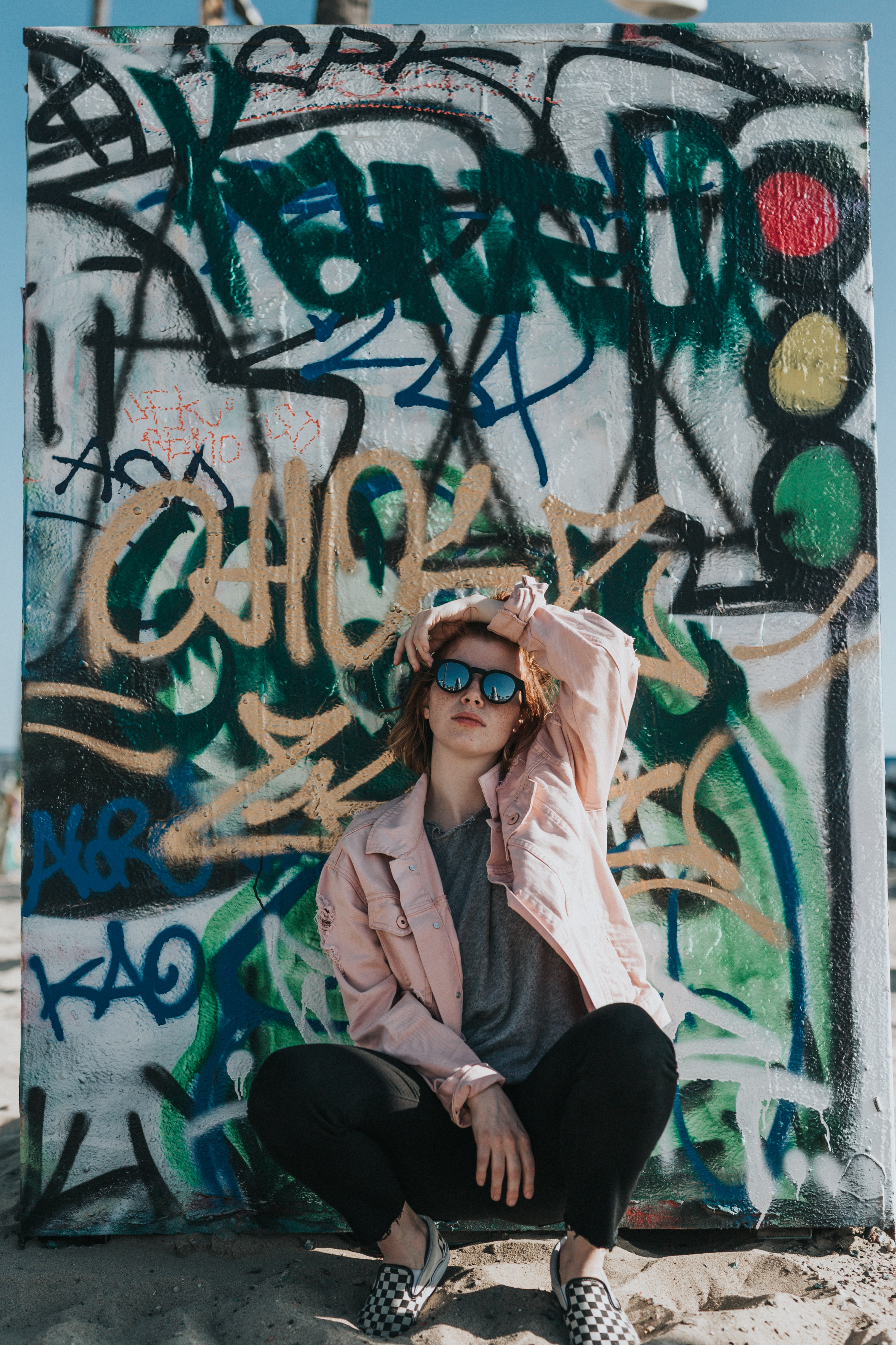 woman wearing pink jacket in front of white wall