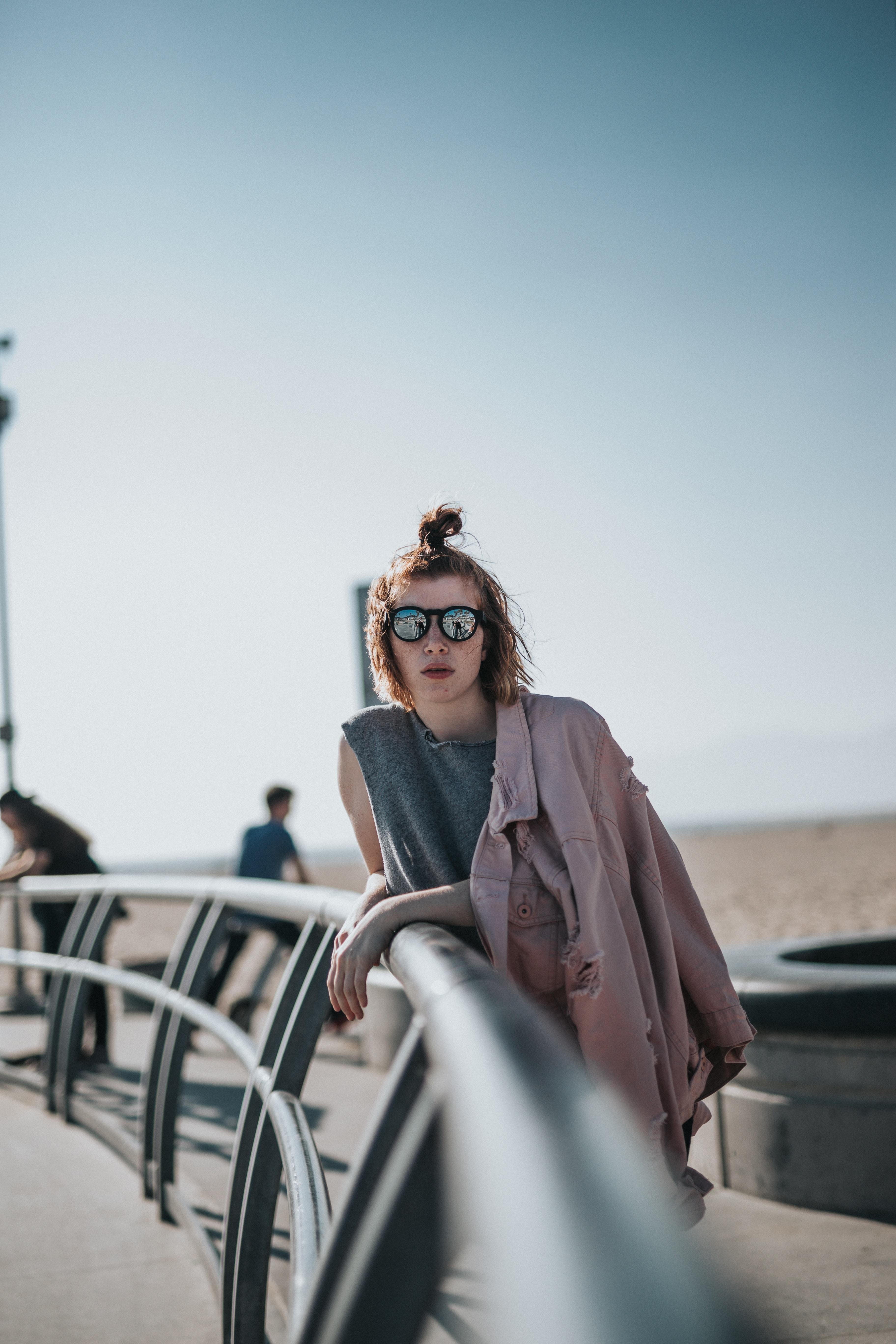 woman standing near railing wearing sunglasses at daytime