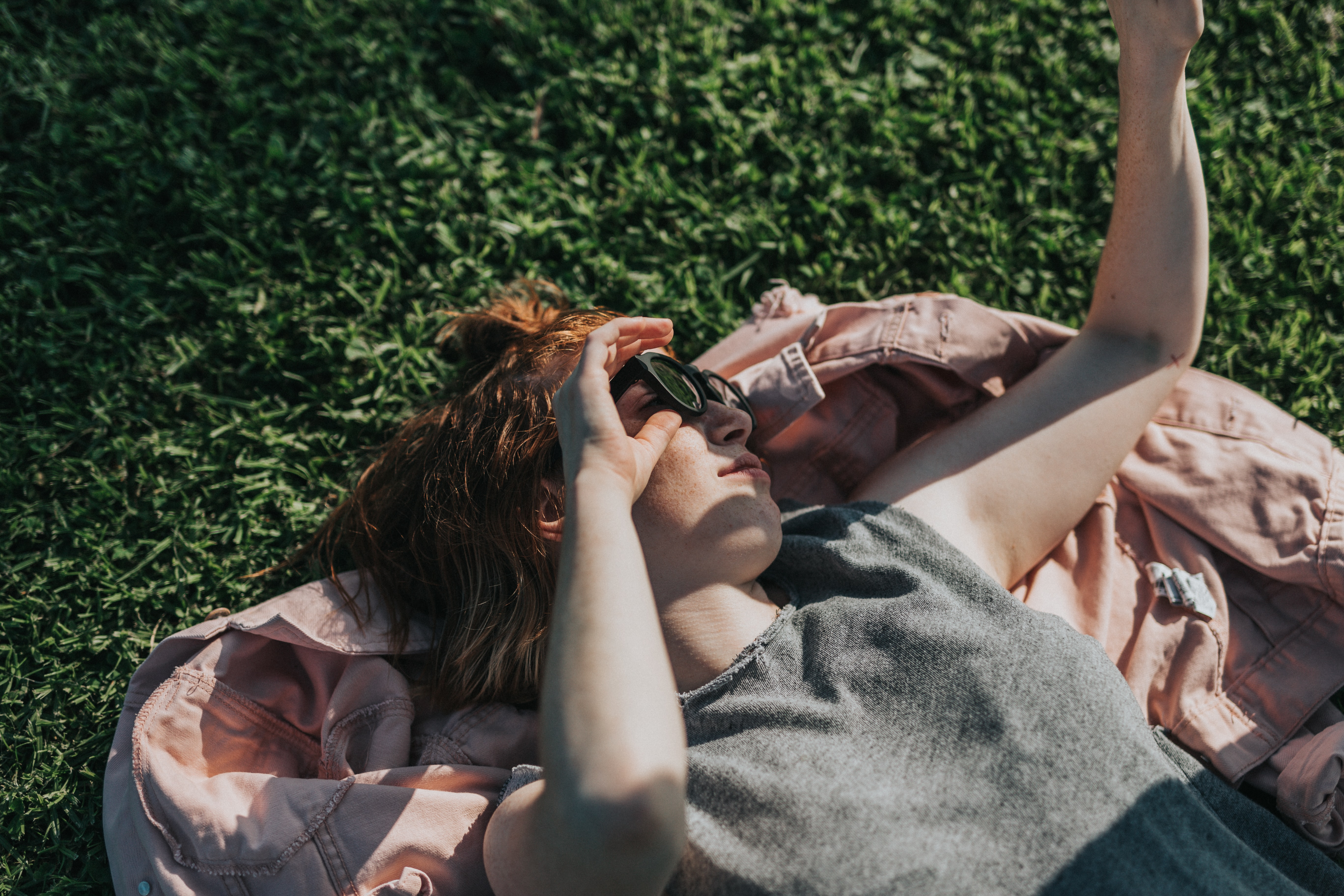 woman lay on grass during daytime