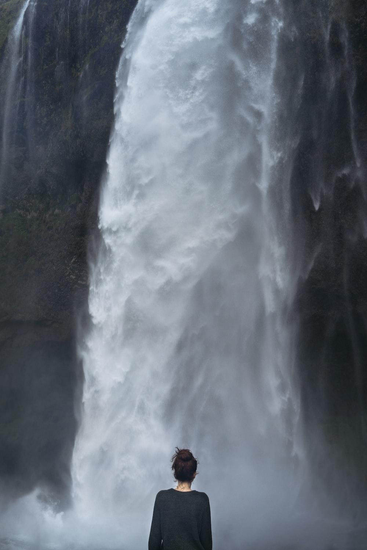 woman in black long-sleeved shirt standing near falls