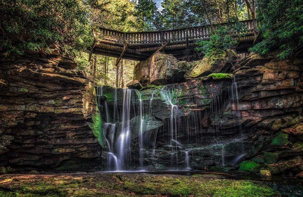 waterfalls near wooden bridge and trees wallpaper