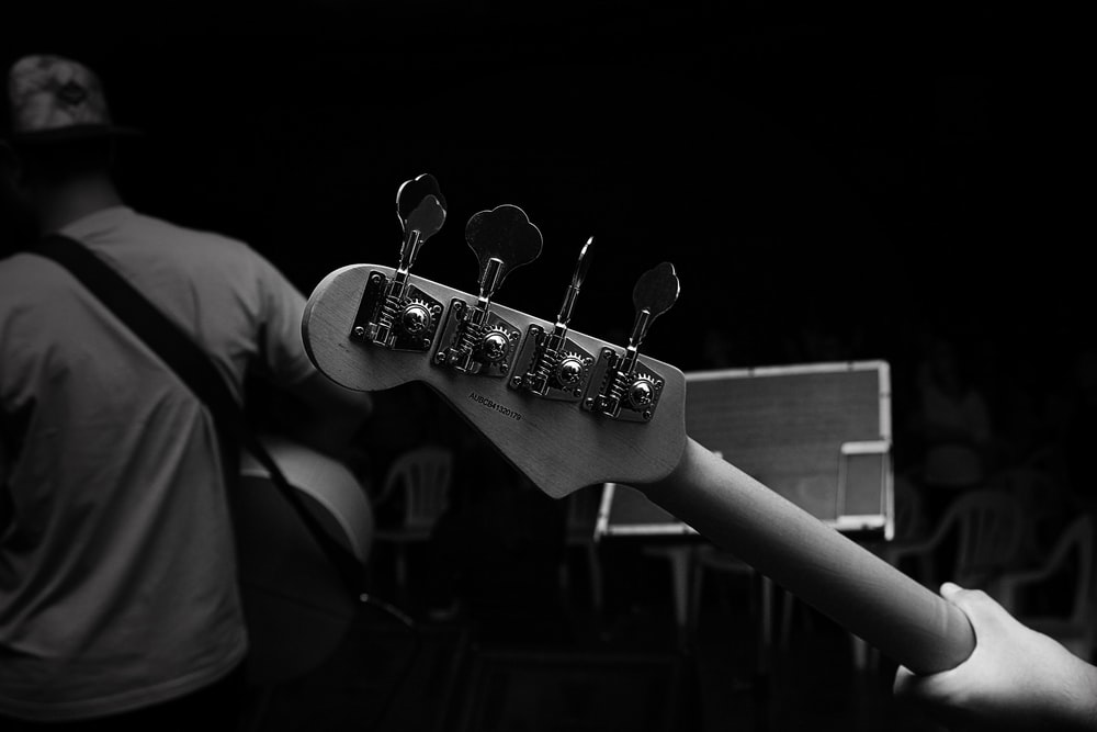 grayscale photography of person carrying guitar