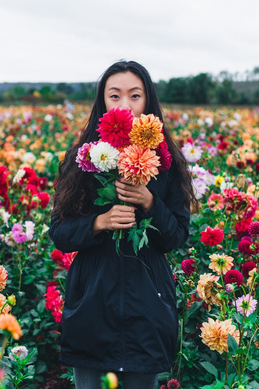 woman wearing black holding flowers during daytime