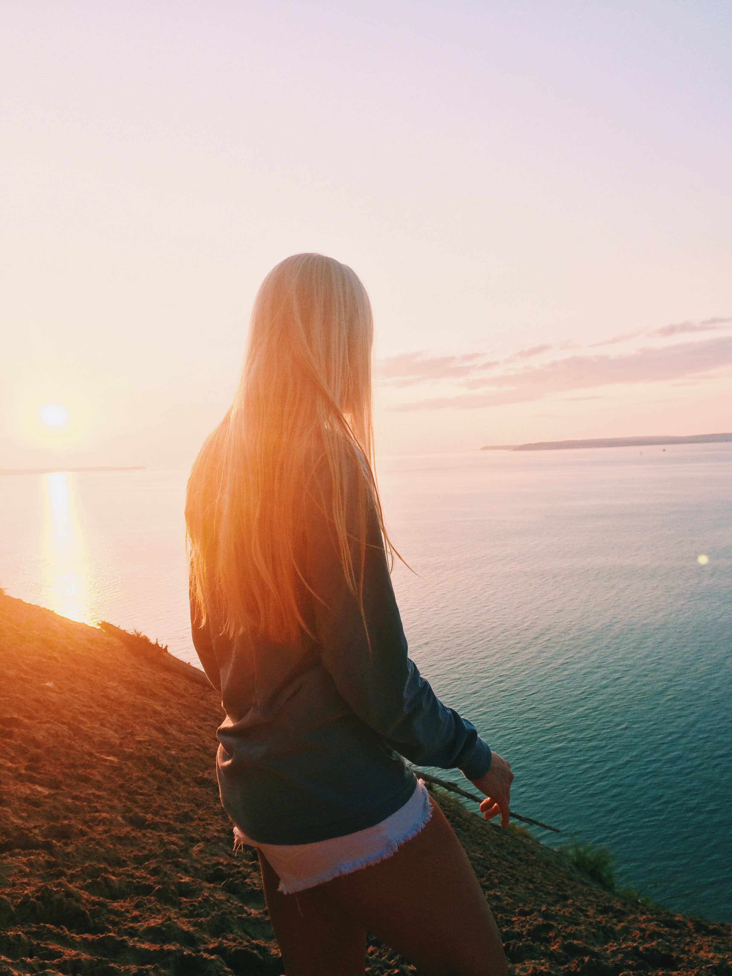 woman stands near body of water during golden hour