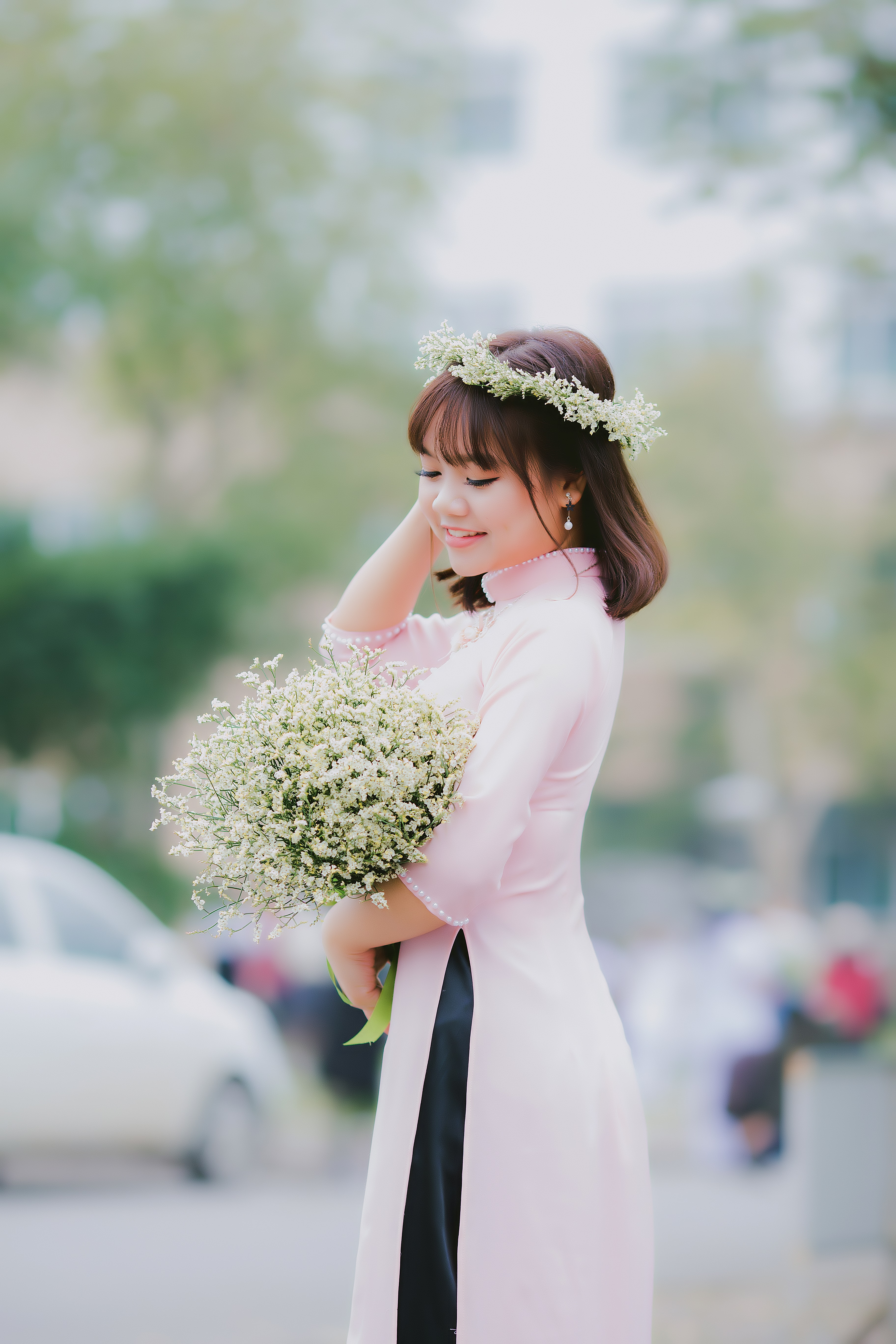 woman holding her hair while carrying white petaled flower bouquet in focus photography