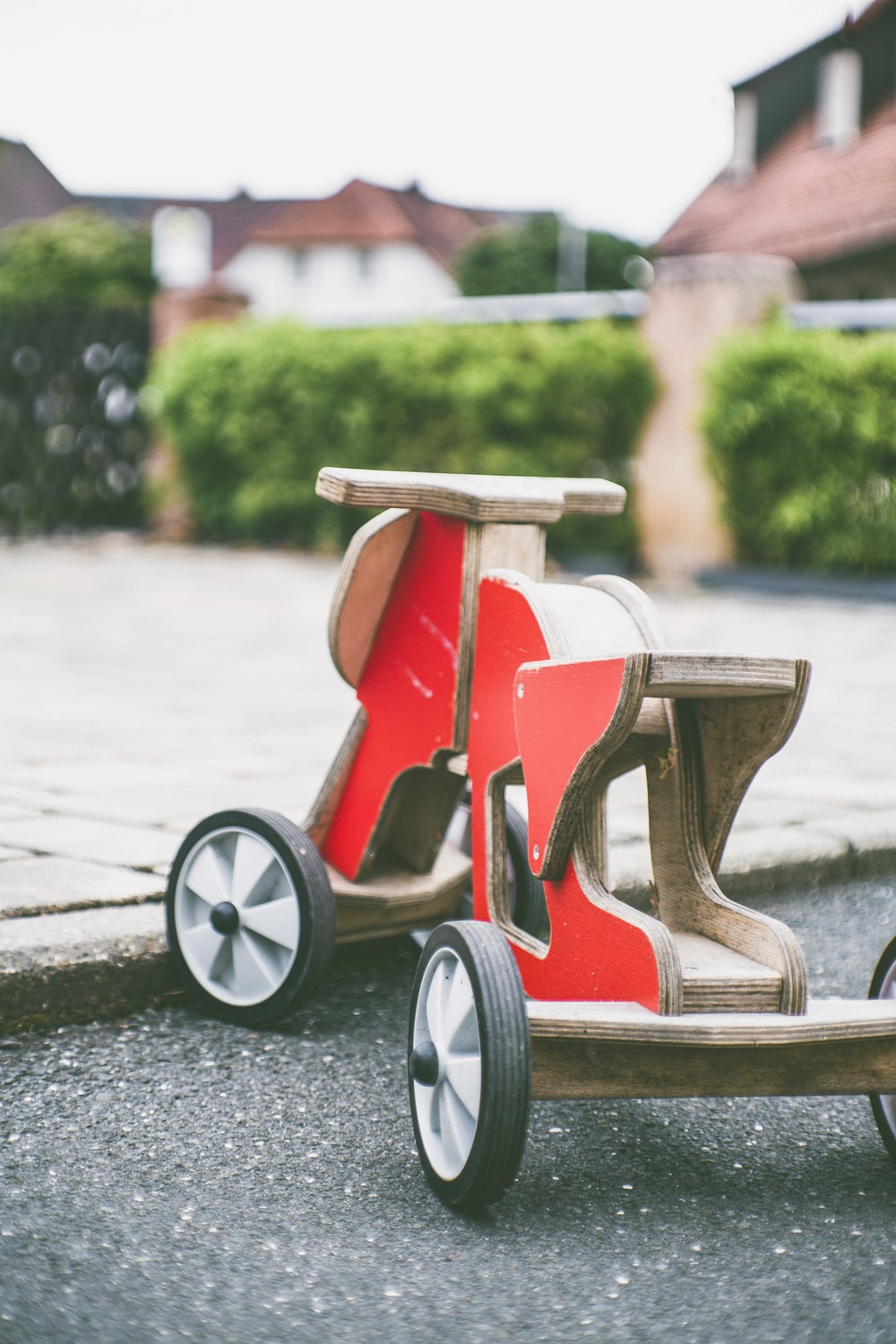 toddler's red and brown wooden ride-on toy on concrete pavement