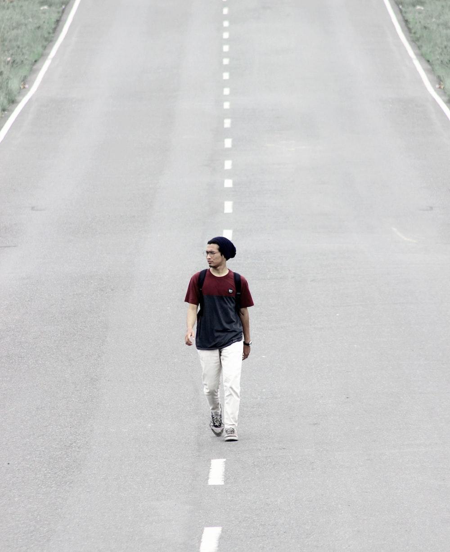 man walking on road at daytime