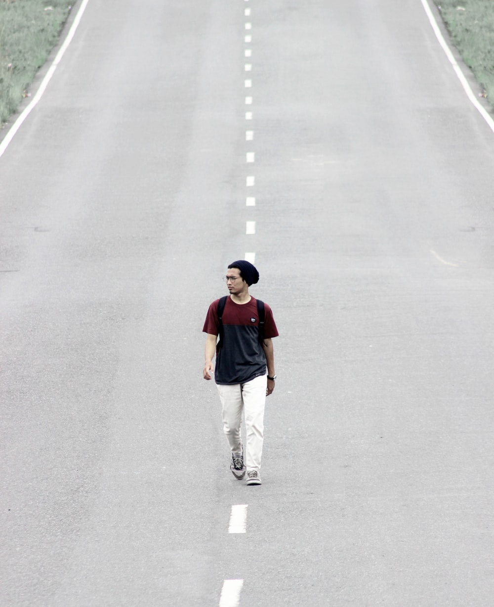 man walking on road at daytime
