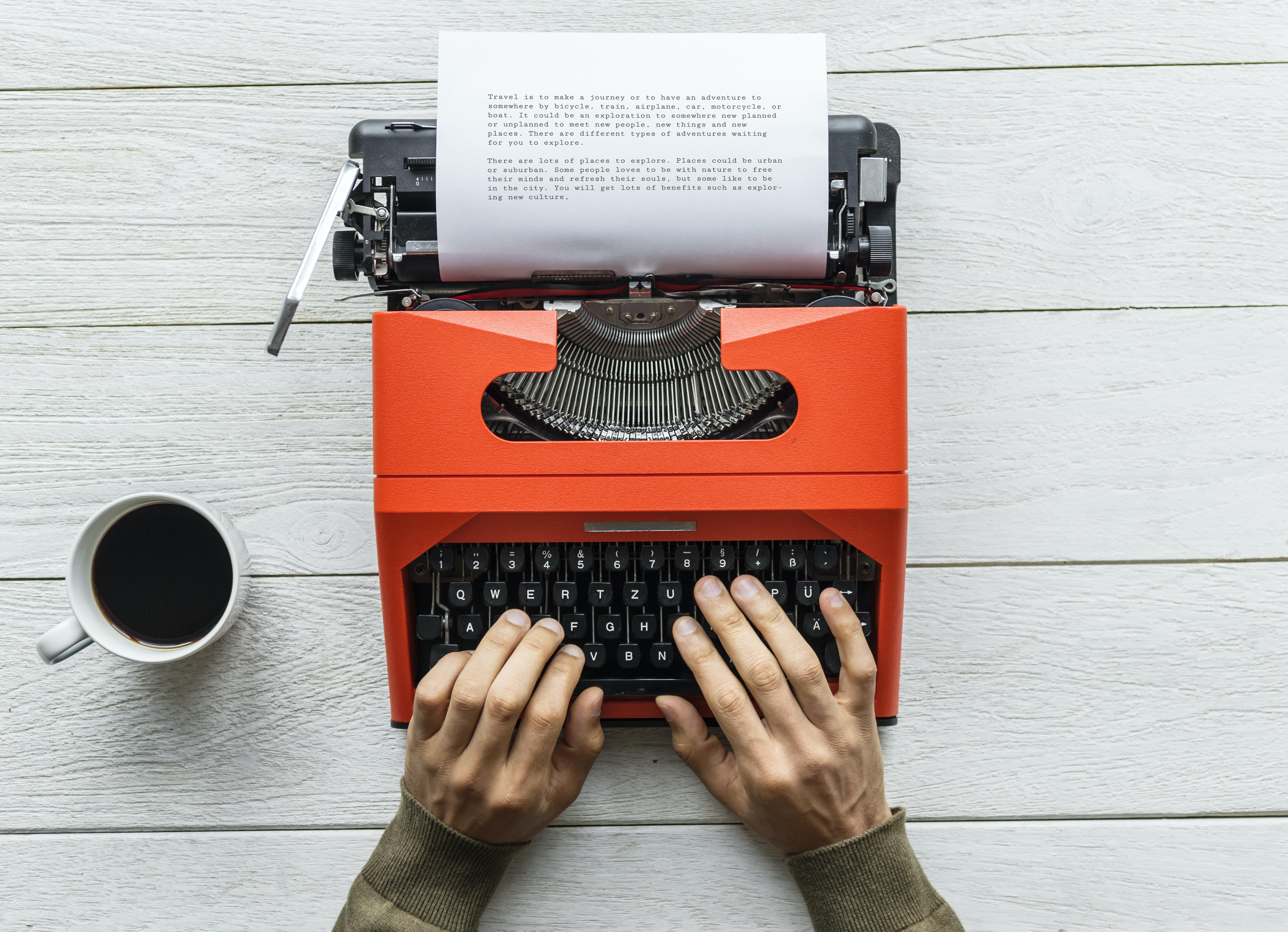 person typing something using red typewriter