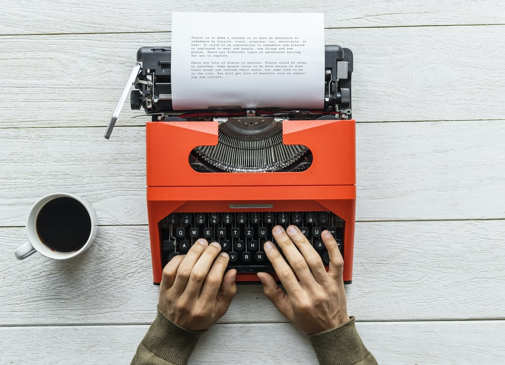 person typing something using red typewriter