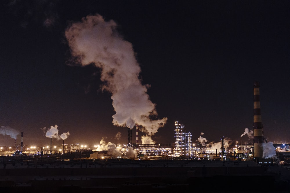 city factories with grey smoke during nighttime